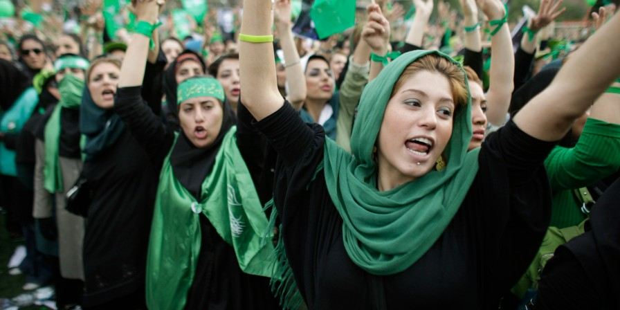 A supporter of main challenger and reformist candidate Mir Hossein Mousavi shouts from the crowd amidst a festive atmosphere at an election rally at the Heidarnia stadium in Tehran, Iran, Tuesday, June 9, 2009. (AP Photo/Ben Curtis)
